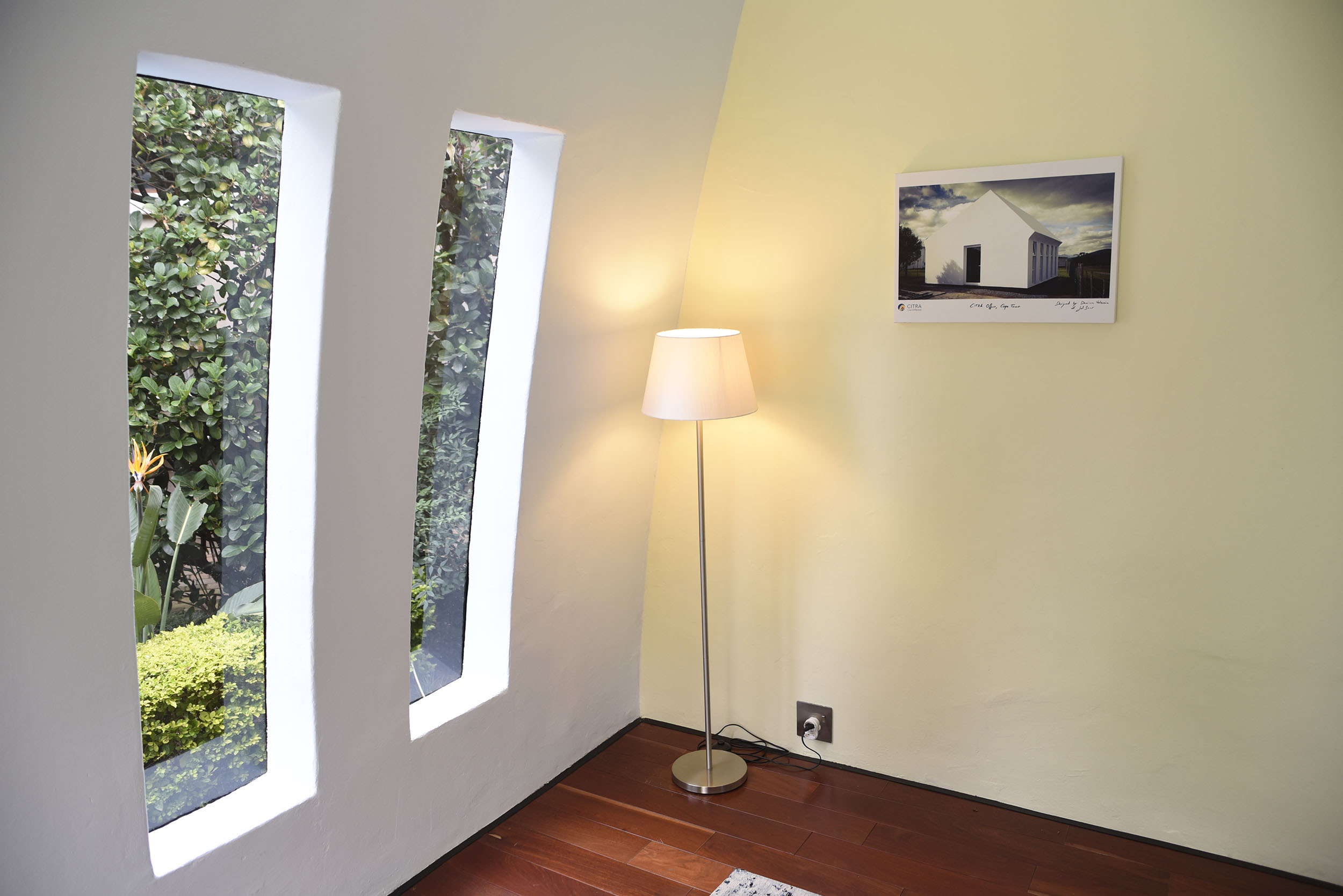 Ambassador's Cottage, inside, lamp, wooden floors and view of the garden